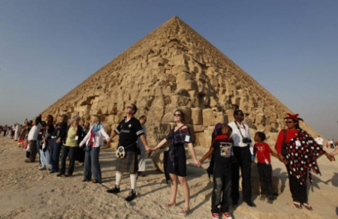 Participants take part in a human chain around the Great Pyramidof Khufu. More than 1500 students, teachers and parents from 50 nationalities formed a circle that symbolized peace in the world. (Photo: Nasser Nasser, AP)